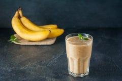 Glas van fruitbanaan - data smoothie met muntbladeren en ingridients op de donkere achtergrond Gezond, vegetarisch, veganistdieet Stock Afbeelding