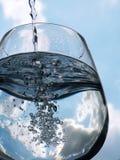 Glas van het gieten van water met bezinning Stock Fotografie
