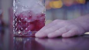 Glas van ijsblokjes, rode drank binnen, hand op de bar Het mengen van vloeistof in het glas stock videobeelden