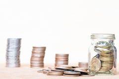 Glas van muntstuk en uitgespreid muntstuk op vloer op vage wijnoogst backgr Stock Foto's