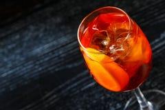 Glas van oranje die cocktail met citroen bij bar tegenachtergrond wordt verfraaid stock foto