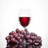Glas van rode die wijn en druif op wit wordt geïsoleerd Stock Foto