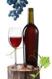 Glas van rode die wijn, fles en druif op stomp op wit wordt geïsoleerd Royalty-vrije Stock Fotografie