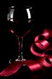 Glas van rode wijn en rood lint Stock Afbeelding
