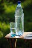 Glas van water en fles met mineraalwater openlucht Royalty-vrije Stock Fotografie