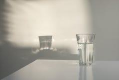 Glas van water met bezinningen Stock Fotografie