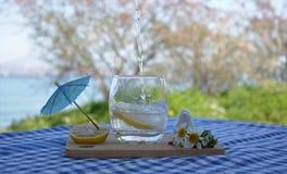 Glas van waterand witte bloemen op houten lijst royalty-vrije stock afbeeldingen