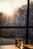 Glas van Wiskyzitting op een houten lijst die sneeuw overzien Stock Afbeelding