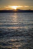 Glas- vatten med den guld- solinställningen bak plana berg i avståndet som ser från Lakesidestranden på Lake Tahoe arkivbild