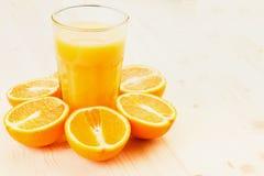Glas vers gedrukt jus d'orange met gesneden sinaasappel halfs stock afbeelding