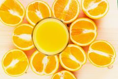 Glas vers gedrukt jus d'orange met gesneden sinaasappel halfs stock foto