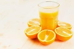 Glas vers gedrukt jus d'orange met gesneden sinaasappel halfs stock fotografie