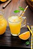 Glas vers gedrukt jus d'orange met ijsblokjes en sinaasappelen op houten lijst Stilleven van de de herfst het comfortabele rustie royalty-vrije stock fotografie