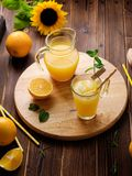 Glas vers gedrukt jus d'orange met ijsblokjes en sinaasappelen op houten lijst Stilleven van de de herfst het comfortabele rustie stock fotografie