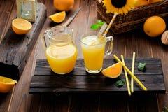 Glas vers gedrukt jus d'orange met ijsblokjes en sinaasappelen op houten lijst Stilleven van de de herfst het comfortabele rustie royalty-vrije stock foto