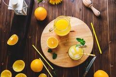 Glas vers gedrukt jus d'orange met ijsblokjes en sinaasappelen op houten lijst Stilleven van de de herfst het comfortabele rustie stock afbeeldingen