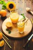 Glas vers gedrukt jus d'orange met ijsblokjes en sinaasappelen op houten lijst Stilleven van de de herfst het comfortabele rustie stock foto's