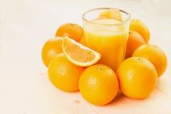 Glas vers gedrukt jus d'orange met sinaasappelen stock afbeeldingen