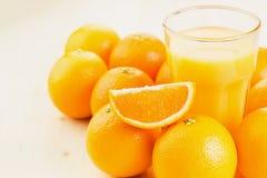 Glas vers gedrukt jus d'orange met sinaasappelen royalty-vrije stock afbeeldingen