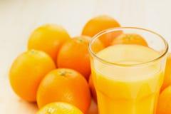 Glas vers gedrukt jus d'orange met sinaasappelen stock afbeelding