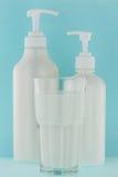Glas verse melk naast witte pompfles van crea van het douchegel Royalty-vrije Stock Afbeeldingen