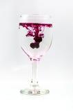 Glas voll vom Wasser mit Tintenfarbe Stockfotos