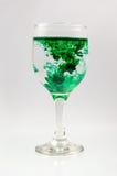 Glas voll vom Wasser mit Tintenfarbe Stockfoto