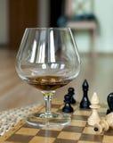 Glas von einem Weinbrand und von einem Schach Lizenzfreies Stockfoto
