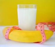 Glas von Milch, von Banane und von Maßband auf einem gelben Hintergrund Konzept der Diät Lizenzfreie Stockfotografie