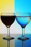 Glas Wasser auf blauem gelbem Hintergrund Lizenzfreie Stockfotos
