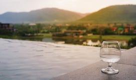 Glas Wasser auf Boden nahe Pool im modernen Landhaus mit Bergblick, Seeblick stockfotografie