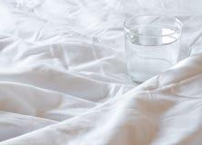 Glas Wasser auf der Decke zerknittert auf Bett lizenzfreie stockfotos