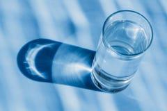 Glas Wasser auf einem blauen Hintergrund Stockfotos