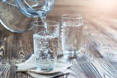 Glas Wasser auf einem Holztisch Stockfotos