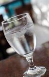 Glas Wasser auf einer Tabelle lizenzfreie stockbilder