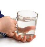 Glas Wasser in den Kinderhänden Stockfotografie