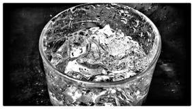 Glas Wasser in der Dunkelheit Lizenzfreies Stockfoto