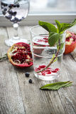 Glas Wasser mit Eis-, Minzen- und Granatapfelsamen auf einem hölzernen Lizenzfreies Stockfoto
