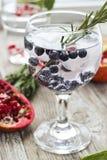 Glas Wasser mit Eis, Rosmarin und Blaubeere auf einem hölzernen tabl Lizenzfreie Stockbilder