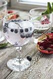 Glas Wasser mit Eis und Blaubeere auf einem Holztisch Lizenzfreie Stockbilder