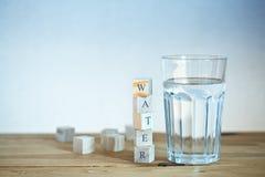Glas Wasser mit Holzklötzen Lizenzfreie Stockfotos
