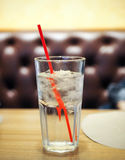 Glas Wasser mit rotem Stroh auf Holztisch Lizenzfreies Stockbild