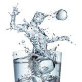 Glas Wasser mit Spritzen als Fußballspieler Stockfotografie