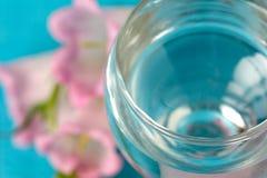 Glas Wasser und Blumen Lizenzfreie Stockfotos