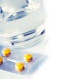Glas Wasser und Pillen Stockbilder