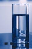 Glas Wasser und Pillen Stockfotos