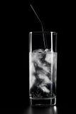 Glas water en ijs op zwarte achtergrond Royalty-vrije Stock Afbeeldingen