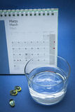Glas water en pillen op blauw wordt geïsoleerd dat Royalty-vrije Stock Foto