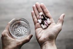 Glas water en pillen in vrouwenhanden, drugsverslaving stock foto's