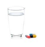 Glas water en pillencapsules Stock Fotografie